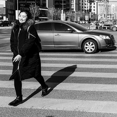 Stolen smile (Go-tea 郭天) Tags: qingdao shandong républiquepopulairedechine cn huangdao beautiful beauty lady woman young cold winter sun sunny shadow smile cars zebra crossing walk walking road lovely pretty happy happiness street urban city outside outdoor people candid bw bnw black white blackwhite blackandwhite monochrome naturallight natural light asia asian china chinese canon eos 100d 24mm prime portrait