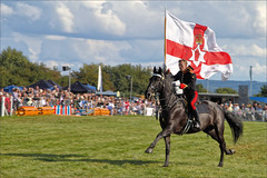 Northern Ireland Leaves the Arena (meniscuslens) Tags: flag northern irlenad horse soldier bucks county show buckinghamshire aylesbury weedon household cavalry musical ride grass arena event sky clouds