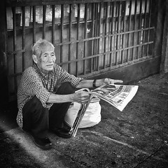 triple flexion (Maureen Bond) Tags: ca maureenbond onthestreets chinatown chinese man paper reading bag bars sitting squatting shinyshoes street photography
