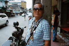 Chinatown Portrait (D. R. Hill Photography) Tags: bangkok thailand thai asia southeastasia chinatown city urban street streetphotography portrait streetportrait man eyecontact amulet film grain analog analogue contax contaxg2 g2 carlzeissplanar35mmf2 35mm 135 35mmfilm zeiss kodak kodakfilm kodakportra400 portra portra400 buddhist buddhism