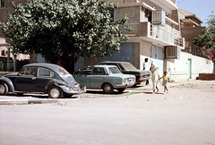 76-228 (ndpa / s. lundeen, archivist) Tags: nick dewolf color photograph by 1976 1970s film 35mm 76 reel76 early1976 africa northernafrica northeastafrica sudan thesudan african sudanese khartoum city town candid streetphotography streetlife citylife people street cars vehicles automobiles parkedcars pedestrian pedestrians headcovering dress woman youngwoman child girl holdinghands building buildings house houses vw volkswagen bug beetle tree airconditioner airconditioners tob hijab tobe