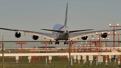 Emirates Airbus A380-861 A6-EDB - Toronto Pearson. (edk7) Tags: nikond300 vivitar135mm128manualfocuslens edk7 2011 canada ontario mississauga torontopearsonairport yyz aviation aircraft plane airplane airliner jet jetliner fourengine emirates airbusa380861 a380 sn013 2008 a6edb landing enginealliancegp7270highbypassturbofan81500lbf landingaids light post fence woodbinegrandstand