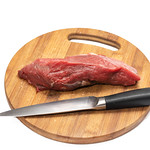 Kitchen knife and beef meat on the round wooden board thumbnail