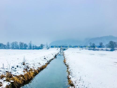 Brook in winter with passing Meridian regional express train near Oberaudorf, Bavaria, Germany