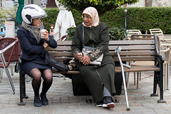 Head coverings (Marion McM) Tags: street women bench seat cafe conversation motorcyclehelmet headscarf headcovering streetportraiture streetphotography casematesquare gibraltar 2019 canoneosm6