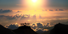 On the top of the world together. A group of people stands on a hill over the beautiful cloudscape. (nithiyabhaskar) Tags: outdoor hiking sunlight adventure hike summit achievement travel arms view climbing sunrise concept stand success himalayas teamwork outside people sun top clouds sunshine team tourist winner group person mountain sunset sky tourism celebrating beautiful background nepal silhouette nature victory man cloudscape accomplishment landscape teamworkconcept