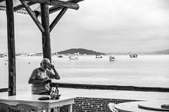 A photographer and the sea... (@petra) Tags: seaside sea boats seascape terrasse tables chairs wall man photographer monochrome nikond600