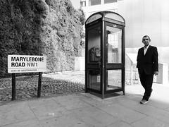 A Man Walking (stevedexteruk) Tags: man smoking cigarette telephone kiosk box marylebone sign road street london uk 2019 blackandwhite mono monochrome bw