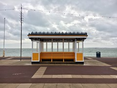 Ready. Just waiting for the start of summer (keith bissett) Tags: wood uk sea england yellow bench waiting cloudy resting ornate southcoast minimalist englishchannel abouttorain personless cold preparation gettingready iphone notyetsummer iphoneography seasonstarting sunbench emptybeach notourists beforetheseason whitepaint mustardyellow empty deserted preseason water seaside pavement path