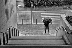 Look, it's raining (ndrearu) Tags: milan milano blacknwhite black white outdoorr raining rain city umbrella stairs street urban canon outside