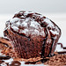 Chocolate muffin with chocolate pieces and icing on white background