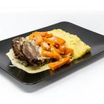bei Lieferdienst bestellter Tafelspitz mit gedämpften Karotten, Kartoffelpüree und Soße auf schwarzem Teller thumbnail