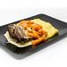 bei Lieferdienst bestellter Tafelspitz mit gedämpften Karotten, Kartoffelpüree und Soße auf schwarzem Teller