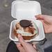 Ein Kronut-Donut aus Blätterteig, mit weißem Schokoguss in einer weißen Burgerbox, aus dem Feinkostgeschäft