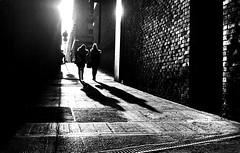 Shine on. (Mister G.C.( Taking a 'Time Out' )) Tags: street urban photography blackandwhite bw minolta minoltahimaticg rokkor rokkor38mm f28 primelens fullframe retro retrocamera zonefocus zonefocusing streetphotography urbanphotography shot image photograph candid people shadows light sunlight sunshine alleyway sidestreet frombehind monochrome town city analog analogphotography analogue 35mm film filmcamera schwarzweiss strassenfotografie mistergc glasgow scotland europe kodak kodakultramax400