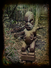 The Maori Carving (Steve Taylor (Photography)) Tags: maori toko tattoo willowbankwildlifereserve sculpture carving fence brown green scary eerie frightening spooky wood wooden man newzealand nz southisland canterbury christchurch plant leaves tree trunk border texture lines
