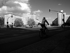 Cycling in Karl Marx Allee (Franco & Lia) Tags: street strasenfotografie fotografiadistrada photographiederue berlin berlino karlmarxallee ddr gdr eastberlin germany deutschland germania biancoenero schwarzundweiss noiretblanc blackwhite