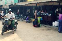 Market street (*Kicki*) Tags: market marketday street candid bike motorbike motorcycle man person people helmet bagan myanmar burma mandalay nyaungu streetlife traffic shopping pagan 50mm facesofmyanmar streetscene manisithumarket longyi foodstall