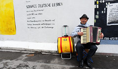 The Accordion Player (Anthony Mark Images) Tags: art text painting wallmurals berlinermauer berlinwall berlin portrait hohner music sitting makingmusic germancolours shinyshoes yellow germanflagcolours germany deutschland europe sidewalk messageingerman male man hat dresspants greyjacket eastsidegallery formereastberlin nikon d850 people accordionplayer smile flickrclickx