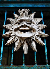 Smiling sun wood carving-house door in Bocos barangay. Banaue-Ifugao-Philippines. 0075 (rweisswald) Tags: smiling sun solardisk face motif decoration ornate wooden woodcarving ancient worship traditional symbol religion tradition folk pagan animistic art ritual myth deity anthropomorphous ray sunbeam openmouth lip eye nose metal metallic rusty oxidized painted blue green grate door gate doorway gateway house mayoyaoroad igorotpeople bocosbarangay banauemunicipality ifugaoprovince cordilleraregion luzonisland philippines
