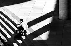 Listening To The Shadows (DobingDesign) Tags: blackandwhite shadows urban berlin headphones sitting steps architecture lines paving geometric waterside germany deutschland stadtmitte street angles stripes listening stairs riverspree river riverside pillar streetphotography contrast