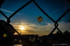 Balloon Sunrise through the fence (subrec) Tags: lakeland florida hot air balloons sunnfun sun n fun international flyin expo colorfulskies colorfulsky colorful color tampabay tampabayarea tampa orlando airshow pentaxk50 pentax pentaxart bluesky fence sunrise