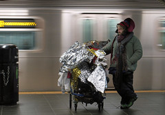 Protective Foil - Times Square Subway Station, NYC (TravelsWithDan) Tags: man homeless shoppingcart tinfoil winter night subway platform underground metro timessquare 42ndstreet passingtrain motionblur protectivefoil candid street nyc manhattan newyork city urban hat coat scarf cold