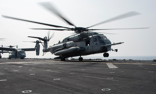 A CH-53E Super Stallion helicopter launches from the flight deck of Wasp-class amphibious assault ship USS Essex