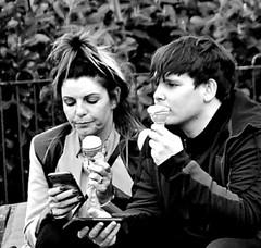 Competing pleasures..... (ronramstew) Tags: liverpool merseyside bw blackandwhite phone cellphone mobilephone icecream cones