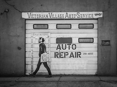 Walk On By (tim.perdue) Tags: auto repair victorian village service garage car door window sidewalk wall man person figure walking street candid black white bw monochrome skancheli zwartwit blanc noir mono monochromatic shades gray grey blanco negro olympus omd em10ii em10mkii mirrorless micro four thirds mft m43 43 tamron 14150mm headphones bag shop cracked sign short north high st columbus ohio downtown urban city mailbox walk by walkonby explore interesting explored interestingness popular