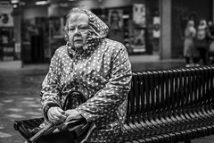 The Cold Bites (Leanne Boulton) Tags: portrait urban street candid portraiture streetphotography candidstreetphotography candidportrait streetportrait eyecontact candideyecontact streetlife sociallandscape old elderly woman female lady eyes face expression mood emotion feeling cold weather winter bench raincoat tone texture detail depthoffield bokeh naturallight outdoor light shade city scene human life living humanity society culture lifestyle people canon canon5dmkiii 70mm ef2470mmf28liiusm black white blackwhite bw mono blackandwhite monochrome glasgow scotland uk