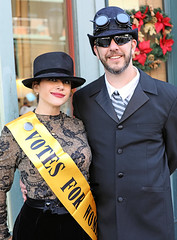 Suffragette And Companion (wyojones) Tags: texas galveston dickensonthestrand christmas holiday festival lady woman girl hat dress brunette sash smile lips browneyes beauty pretty cute pendant earring suffragette womansvote man gentleman googles shades sunglasses suit tie beard steampunk timetravelers airship