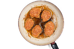 Flat lay above metal pan with frying meatballs in oil