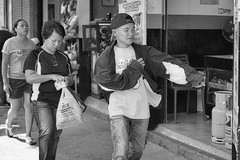 Get it On (Beegee49) Tags: street man putting coat woman pedestrians blackandwhite monochrome bw happy planet luminar sony a6000 silay city philippines asia