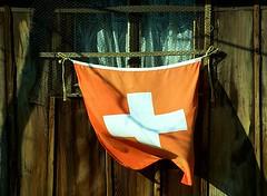 Swiss Flag in a Spring Breeze (Dan Daniels) Tags: switzerland flags wood swissflag gardens chickens roosters woodenhouse chickencoop riehen kantonbaselstadt moostal cantonbaselstadt schweiz breeze