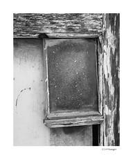 Cliffhanger (agianelo) Tags: weathered wood window pane peeling paint monochrome bw bn blackandwhite