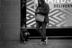 Cornered (Sean Batten) Tags: london england uk europe coventgarden streetphotography street blackandwhite bw child adult people person candid city urban shopwindow delivery fuji x100f fujifilm