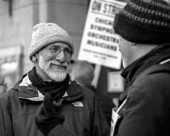 Friendly face (kristenscotti) Tags: olympus chicago chicagoland evanston usa blackandwhite bw black white streetphotography street spring winter bokeh capturestreets visuals microfourthirds 50mm portrait outside art city people monochrome penf mono exterior day strike man sign orchestra symphony glasses hat friends face absoluteblackandwhite