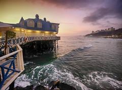 Sunset in Lima, Peru (` Toshio ') Tags: toshio lima peru southamerica larosanautica miraflores pacificocean ocean sea sunset jetty wave cloud architecture restaurant fujixt2 xt2