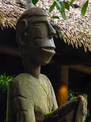 A Wooden Smile (Steve Taylor (Photography)) Tags: thatchedroof scar head sculpture carving restaurant brown green smile smiling man asia singapore leaves texture zoo