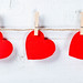 Red hearts hanging on clothespins on white wooden background