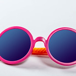 Sunglasses pink-orange colors on white. Kid's party concept thumbnail