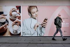 Caught on camera (Silver Machine) Tags: salisbury wiltshire streetphotography street candid candideyecontact man walking billboard girl phone poster headphones fujifilm fujifilmxt10 fujinonxf35mmf2rwr