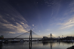 Two Bridges and a Crescent Moon (16/36 Sydney Harbour Bridge) (astrogirl969) Tags: fujifilm xpro2 samyang12mmf20ncssc sydney anzacbridge sydneyharbourbridge moon crescent water reflection morning dawn circularpolarizingfilter clouds colour pink blue sunrise structure postprocessed photoshop lightroom distortioncorrection cityskyline city silhouette velvia filmsimulation outdoor harbour tranquil peaceful lights boats 10faves 500views