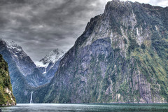 The Lion (myshutterworld) Tags: newzealand south island landscape mountains peaks serene picturesque gorgeous southland milfordsound hdr spectacular beautiful mind blowing amazing middle earth heavenonearth lake fiordlandnationalpark cloudy dark blue green water nature sky grass trees rocks fiord lion snowcapped