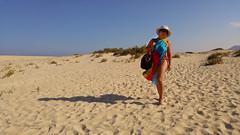 Crossing dunes (piotr_szymanek) Tags: fuerteventura marzka woman milf outdoor beach blue sky sand hat glasses sunglasses naturist legs feet face eyesoncamera pareo nobra nopants 1k 20f 5k
