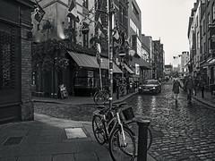 Streets of Dublin (kristenscotti) Tags: olympus usa blackandwhite bw black white streetphotography street spring winter bokeh capturestreets visuals microfourthirds 50mm portrait outside art city people monochrome penf mono exterior day absoluteblackandwhite dublin ireland couple bike bicycle cycle