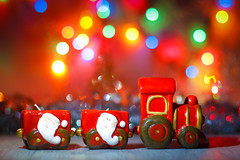 Toy Steam Train with Santa Claus on a background of golden garlands and blur of colored lights. (AlestrPhoto) Tags: new year background happy holiday card merry frame greeting white blue festive decoration view tree silver gift eve star invitation postcard wooden seasonal flatlay top bokeh bright winter red wood light glitter december snowman close up snow closeup space copy green toy concept decorative season decor ball pine fir