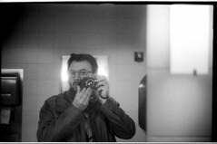 1930LeicaSummar_TMAX100_509 (Johnny Martyr) Tags: selfportrait selfie photographer filmphotographer 1930 leica leitz germancamera vintagecamera antiquecamera 35mmfilmcamera takingapicture mirror camera rangefinder 35mm film bw summar kodak lines composition eyeglasses hipster nerd bathroom self reflection barnack ltm thread mount screw leicascrewmount antiqueleica vintageleica classiccamera leicaglow vitnage vintage classic retro old viewfinder brightline 5cm 50mm 1930s