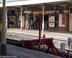 Off To London (M C Smith) Tags: platform platforms people standing train station london chingford pentax k3 white black orange letters numbers symbols shadows buffers canopy columns red advertising barriers posters lights woman man men blue pink signs arrow track